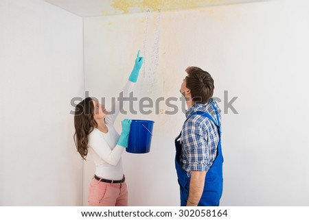 Young Woman With Bucket Showing Water Leaking From Damage Ceiling To Maintenance Guy