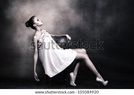 young woman with bun styled hair in elegant dress pose on chair, studio shot