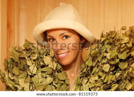 Young woman with bunches of green birch twigs