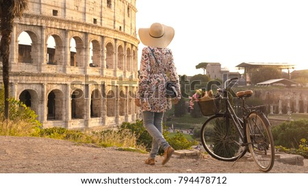 Young woman with bycicle takes pictures of the colosseum in rome at sunset with smartphone. Stylish dress with large hat, flowers and bread in basket.