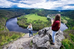 Young woman with camera take photo girl. Blogger photoshoot concept. Tourist travels. Beautiful outlook on the Vltava river, mountains and hills during sunset from the the viewpoint Altan.
