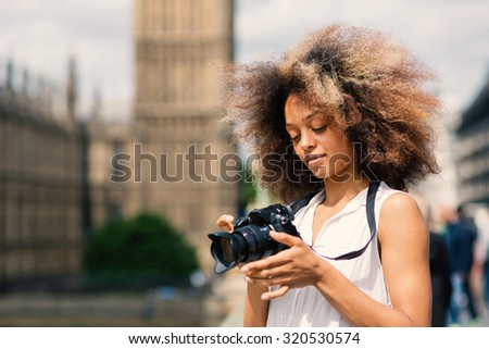 Young woman with camera taking photos in London on Westminster bridge on a sunny day. Filtered image.