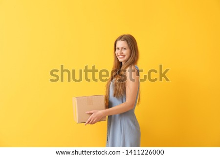 Young woman with cardboard box on color background