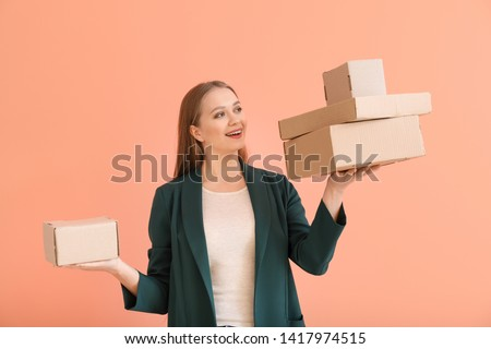 Young woman with cardboard boxes on color background