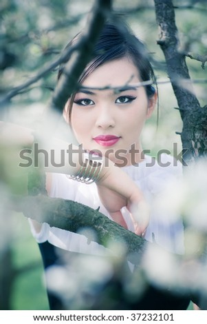 Young woman with cherry flowers portrait. Bright soft colors.