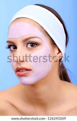Young woman with clay facial mask on blue background