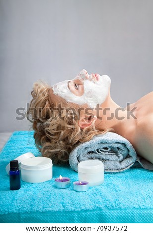 Young woman with clay facial mask. Spa treatment