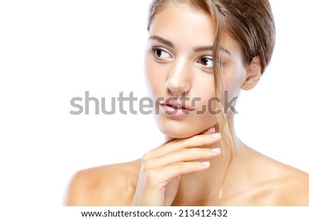 Young woman with clear face natural make up her hair up touching chin with her hand on a white background  #213412432