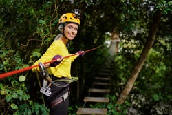 Young woman with climbing gear in an adventure extreme park climbing or passing on the rope road.