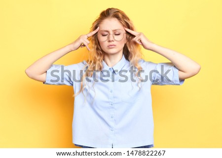 young woman with closed eyes and serious expression concentrated onthinking process. serious girl touching her temples with fingers . girl with headache massaging her head