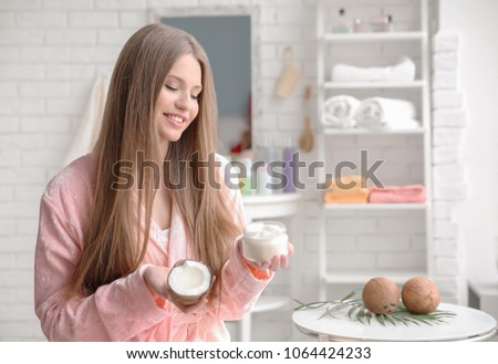 Young woman with coconut oil for hair in bathroom