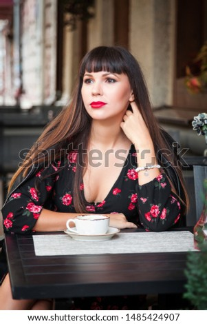 Young woman with coffee sitting at outdoors café #1485424907