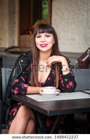 Young woman with coffee sitting at outdoors café #1488452237