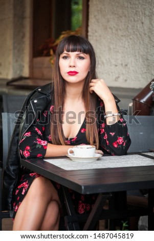 Young woman with coffee sitting at outdoors cafe #1487045819