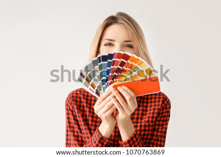 Young woman with color palette on white background
