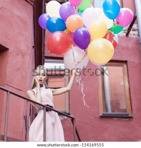 young woman with colorful balloons surprised on a street - outdoors