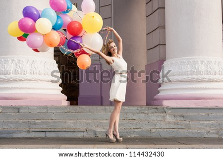 Young woman with colorful latex balloons keeping her dress, urban scene, outdoors