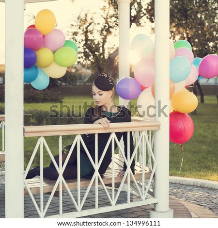 Young woman with colorful latex balloons, outdoor - stock photo
