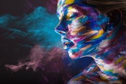 Young woman with colorful make-up and body art on a black background with multi-colored smoke