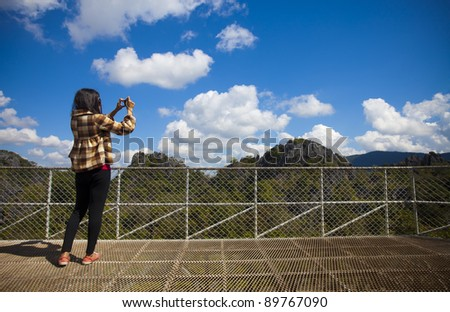 Young woman with compact camera, standing on cliff's edge and taking a photo