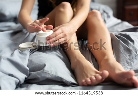 Young woman with cream for feet sitting on bed