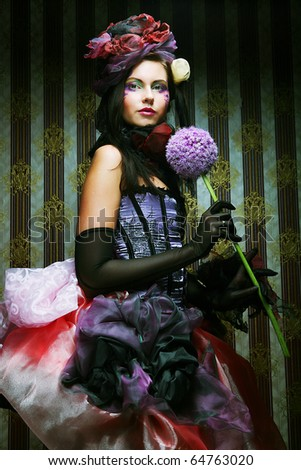 young woman with creative make-up in doll style with flower