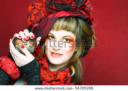 Young woman with creative make-up in red hat. - stock photo