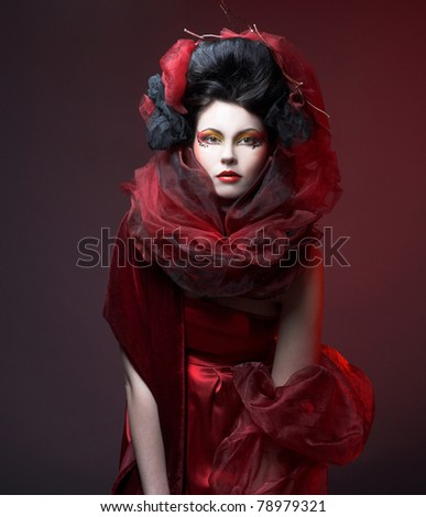Young woman with creative visage in red dress and  shawl.
