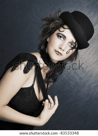 Young woman with creative visage in vintage hat and black glove