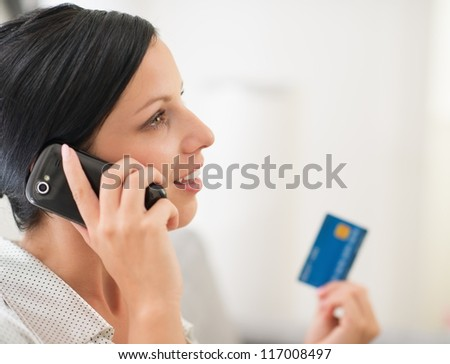 Young woman with credit card and speaking mobile phone - stock photo