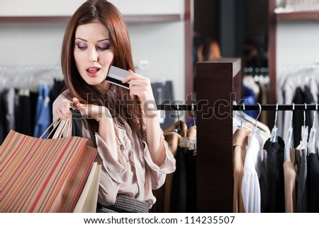 Young woman with credit card is in the shop