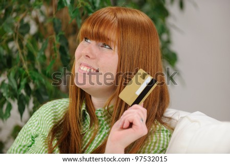 young woman with credit card smiling at home - stock photo