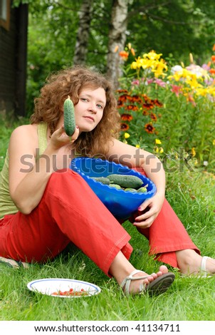 Young woman with crop of cucumbers in garden