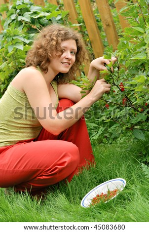 Young woman with crop of red currant in garden