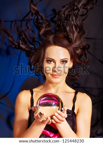 Young woman  with crystal ball. Halloween.