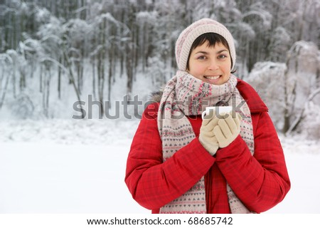 Young woman with cup in winter park