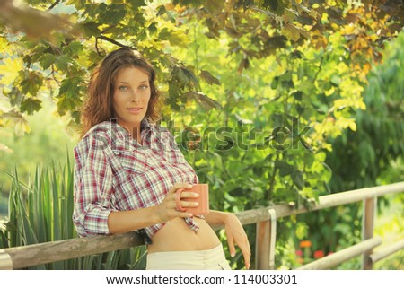 Young woman with cup of coffee enjoy the sunset