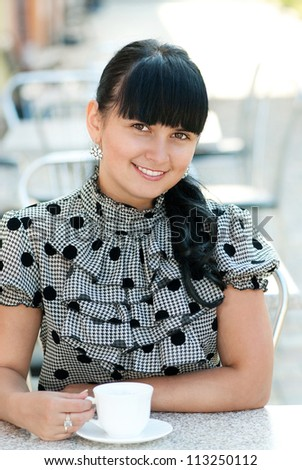 Young woman with cup of coffee in street cafe