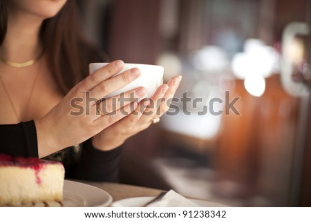 young woman with cup of italian coffee cappuccino in cafe restaurant