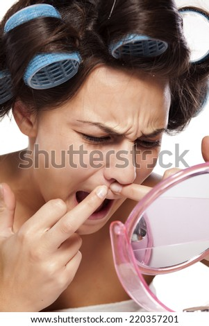 young woman with curlers squeezing pimple on her mustache