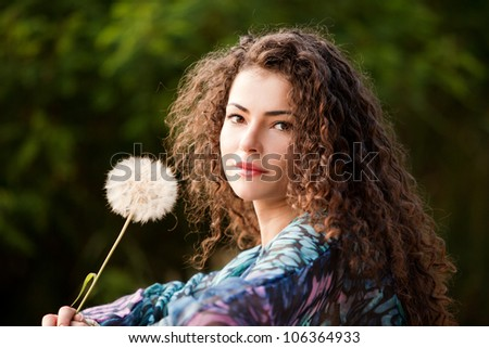 young woman with curly hair hold butter cup flower outdoor portrait