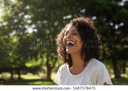 Young woman with curly hair laughing while standing outside in a park on a sunny summer afternoon