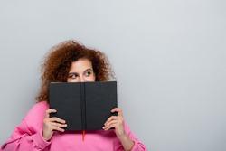 young woman with curly hair obscuring face with notebook isolated on grey