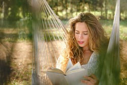 Young woman with curly hair sitting on hammock and reading interesting book on sunny weekend day in garden