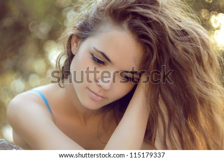Young woman with curly hairs outdoors portrait. Soft sunny colors.
