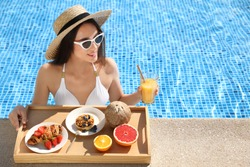 Young woman with delicious breakfast on tray in swimming pool. Space for text