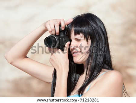 Young woman with digital photocamera