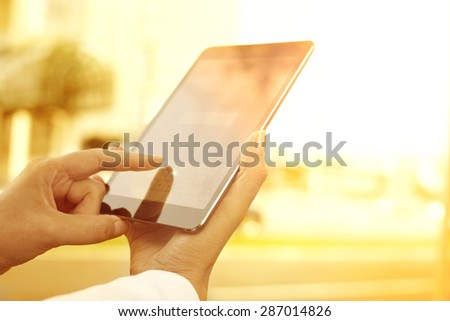 Young woman with digital tablet in the city.A young woman is holding a digital tablet. The image is taken in the city. The face of the young woman is not visible.