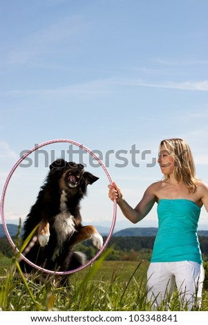 Young woman with dog and tires on a lawn. In the background mountains