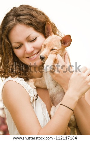 Young woman, with dog, looking happy and smiling